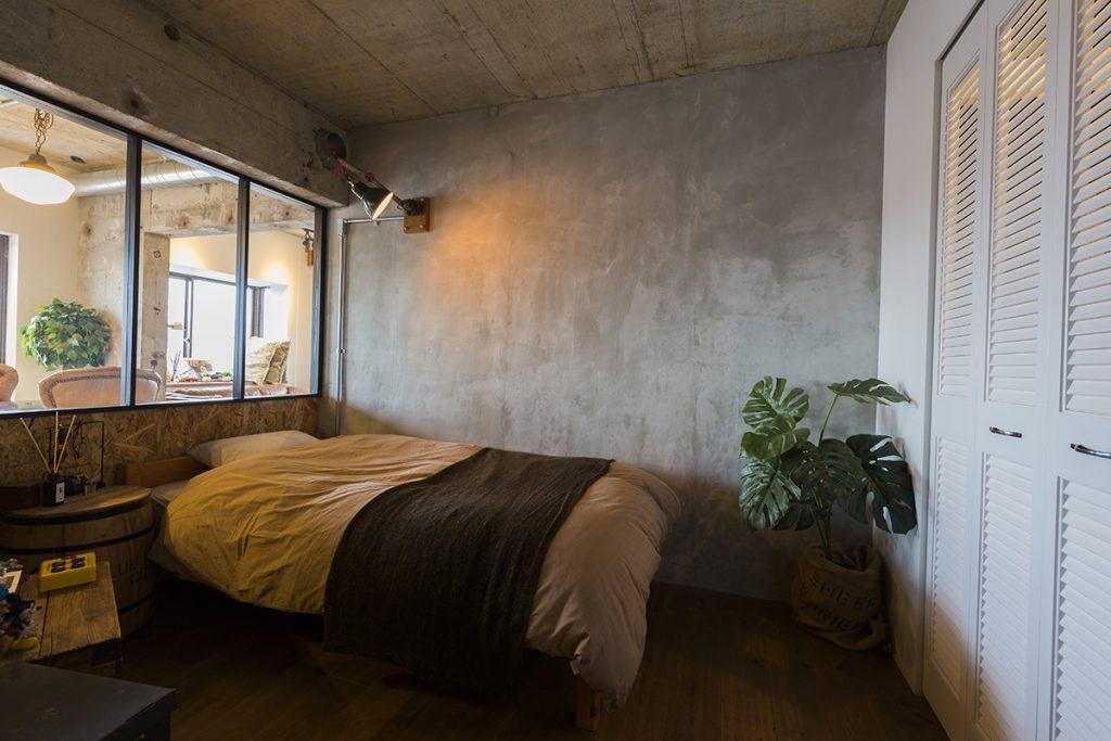 室内窓が特徴の寝室、奥の壁にはビンテージの照明も